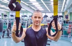 Uomo che fa addestramento della sospensione con le cinghie di forma fisica fotografia stock