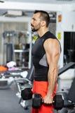 Uomo che fa allenamento con le teste di legno pesanti Fotografia Stock