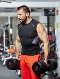 Uomo che fa allenamento con le teste di legno pesanti Immagini Stock