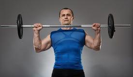 Uomo che fa allenamento della spalla con il bilanciere Fotografie Stock Libere da Diritti