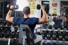 Uomo che fa allenamento della spalla nella palestra Fotografia Stock