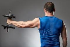 Uomo che fa allenamento della spalla in studio Fotografia Stock Libera da Diritti