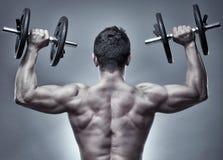 Uomo che fa allenamento della spalla in studio Fotografia Stock