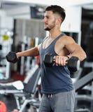 Uomo che fa allenamento della spalla in una palestra Immagini Stock