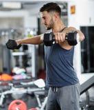 Uomo che fa allenamento della spalla in una palestra Fotografie Stock Libere da Diritti