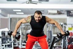 Uomo che fa allenamento della spalla in una palestra Fotografia Stock