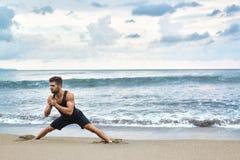 Uomo che fa allungando gli esercizi di allenamento, esercitantesi alla spiaggia Forma fisica Fotografia Stock Libera da Diritti