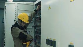 Uomo che fa attrezzatura di conteggio elettrica video d archivio