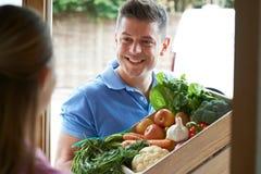 Uomo che fa consegna a domicilio della scatola di verdure organica fotografie stock