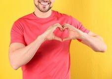 Uomo che fa cuore con le sue mani sul fondo di colore fotografia stock
