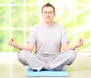 Uomo che fa esercitazione di yoga sulla stuoia Immagini Stock Libere da Diritti