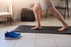 Uomo che fa esercizio del corpo e che risolve a casa Immagine Stock