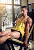 Uomo che fa estensione della gamba in palestra Immagini Stock