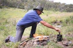 Uomo che fa fuoco di accampamento fotografie stock