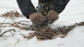 Uomo che fa fuoco di accampamento in neve video d archivio