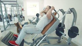 Uomo che fa gli edifici occupati in macchina dell'incisione mentre donna che fa la stampa della gamba