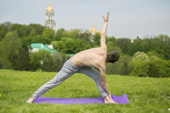 Uomo che fa gli esercizi di yoga nel parco Fotografia Stock