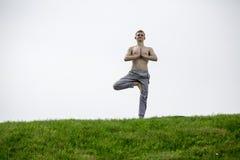 Uomo che fa gli esercizi di yoga nel parco Fotografie Stock