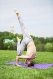 Uomo che fa gli esercizi di yoga nel parco Fotografie Stock Libere da Diritti