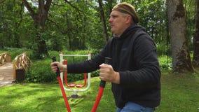 Uomo che fa gli esercizi sulla macchina passo passo video d archivio