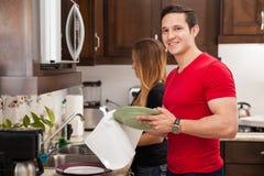 Uomo che fa i piatti con la sua ragazza immagini stock libere da diritti