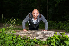Uomo che fa i piegamenti sulle braccia su un albero di menzogne Fotografie Stock