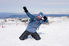 Uomo che fa il segno di vittoria dopo il risultato di punta di trekking della sommità in montagna della neve sul paesaggio di inv Fotografie Stock Libere da Diritti