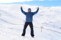 Uomo che fa il segno di vittoria dopo il risultato di punta di trekking della sommità in montagna della neve sul paesaggio di inv Fotografia Stock Libera da Diritti