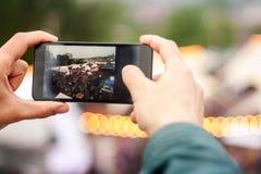 Uomo che fa immagine in via con il telefono cellulare Fondo del bokeh di festival della via fotografie stock