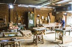 Uomo che fa lavorazione del legno in carpenteria Gruppo di lavoro di carpenteria fotografia stock