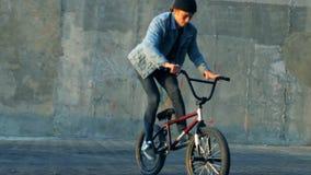 Uomo che fa le acrobazie con una bici in uno skatepark, movimento lento archivi video