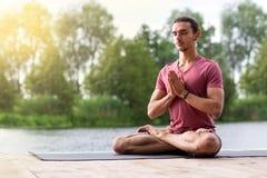 Uomo che fa meditazione di yoga in natura vicino al fiume Copi lo spazio fotografie stock libere da diritti