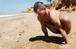 Uomo che fa posizione di yoga del pendolo Immagine Stock