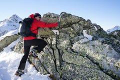 Uomo che fa trekking di inverno nelle montagne Fotografie Stock