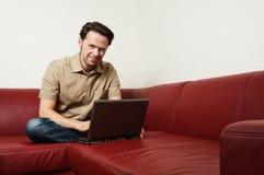 Uomo che fa un certo worh del computer portatile a casa Immagini Stock
