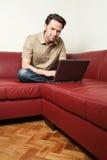 Uomo che fa un certo worh del computer portatile a casa Fotografia Stock Libera da Diritti