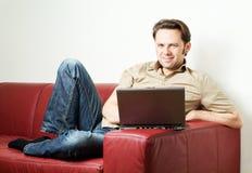Uomo che fa un certo worh del computer portatile a casa fotografie stock