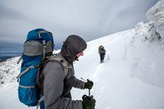 Uomo che fa un'escursione in montagne di inverno prima del temporale Fotografia Stock Libera da Diritti