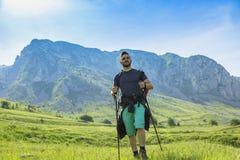 Uomo che fa un'escursione in montagne verdi Fotografia Stock