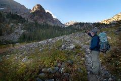 Uomo che fa un'escursione sulla foto del fianco di una montagna con lo Smart Phone Immagine Stock Libera da Diritti