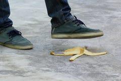 Uomo che fa un passo sulla pelle di banana o sulla buccia, concetto di incidente fotografia stock
