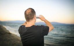 Uomo che fa una foto sulla spiaggia immagine stock libera da diritti