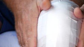 Uomo che fa una nuova e fasciatura pulita su una ferita del piede video d archivio