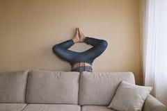 Uomo che fa yoga dietro lo strato beige Immagini Stock Libere da Diritti