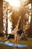 Uomo che fa yoga nella foresta di autunno immagini stock