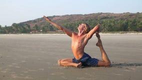 Uomo che fa yoga sulla spiaggia video d archivio