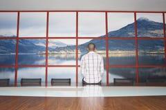 Uomo che fissa alla foto della parete nell'auditorium Fotografia Stock