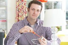 Uomo che fissa spina elettrica sulla lampada a casa Fotografie Stock