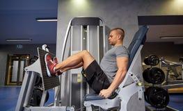 Uomo che flette i muscoli della gamba sulla macchina della palestra Immagini Stock Libere da Diritti