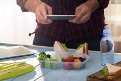 Uomo che fotografa la scatola di pranzo con alimento sano Fotografia Stock